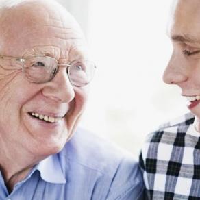 En äldre man skrattar tillsammans med hemtjänstpersonal. Foto.