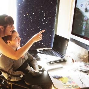 Pojke tittar på en TV-skärm tillsammans med assistent. Foto.